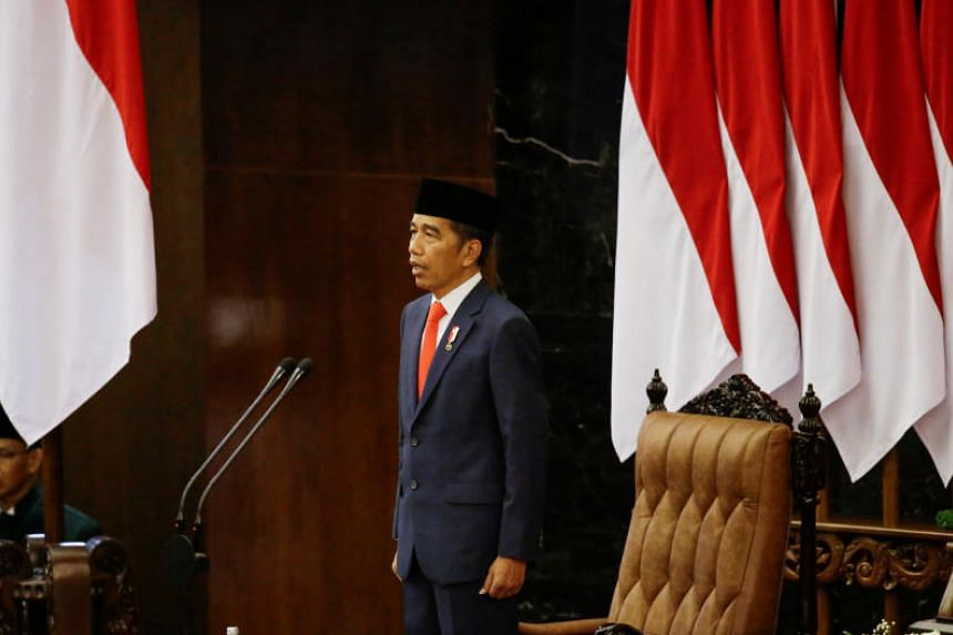 Indonesian President Joko Widodo standing at attention for the national anthem after taking an oath during his presidential inauguration for the second term, at the House of Representatives building in Jakarta on Oct 20, 2019.