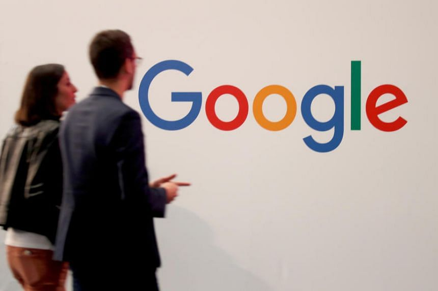 In a file photo taken on May 16, 2019, visitors pass by the logo of Google at the high profile start-ups and high-tech leaders' gathering, Viva Tech, in Paris.
