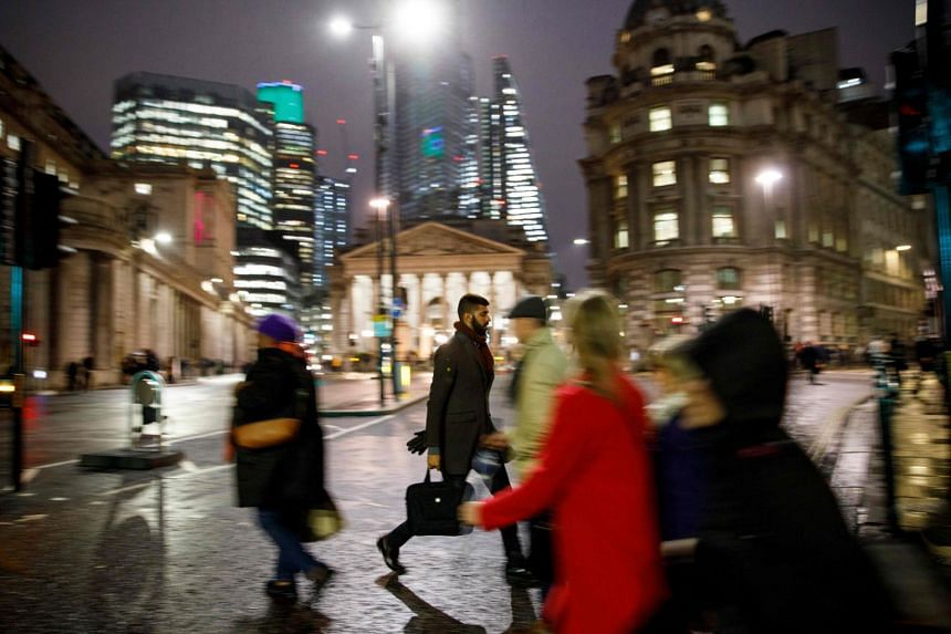 A 2018 photo shows people making their way home through drizzle in the City of London.