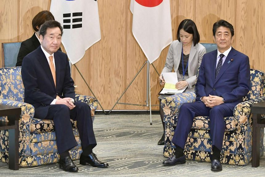 South Korean Prime Minister Lee Nak-yon (left) met Japanese Prime Minister Shinzo Abe amid a bitter feud over history and trade.