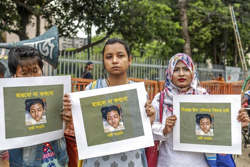 In this photo taken on April 12, 2019, women hold placards with a photograph of schoolgirl Nusrat Jahan Rafi at a protest in Dhaka.