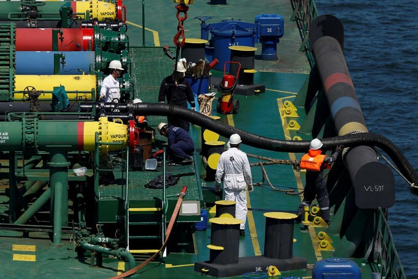 Crew members work on board a ship off Jurong Island, on July 11, 2019. Singapore aims to be one of the top countries with the safest and healthiest workplaces and to reduce the workplace fatal injury rate to below one for every 100,000 workers.
