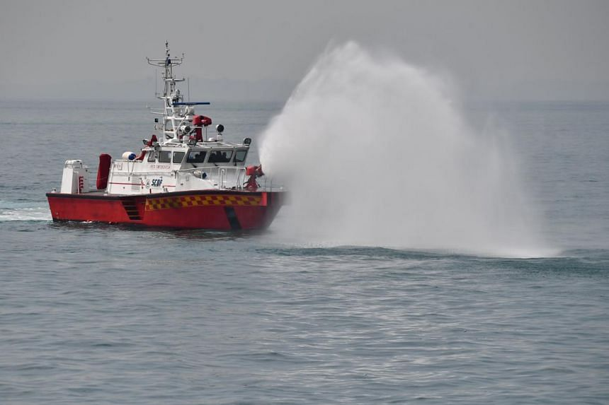 "SCDF's Rapid Response Fire Vessel (RFV) Red Swordfish, creating a ""water curtain"" via their onboard water monitors to disperse ""chemical fumes""."