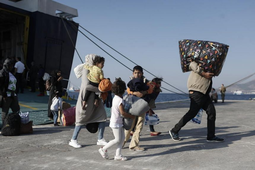 A photo taken on Oct 22 shows migrants from Samos Island disembarking from a ferry at the port of Elefsina near Athens.