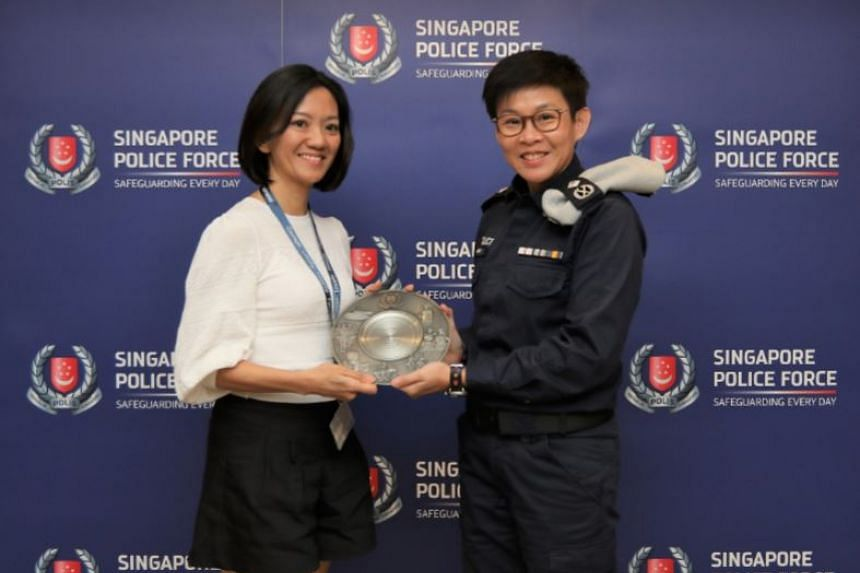 Ms Chiang Su Sia receiving her Public Spiritedness Award from Assistant Commissioner Evon Ng, Deputy Commander of TransCom.