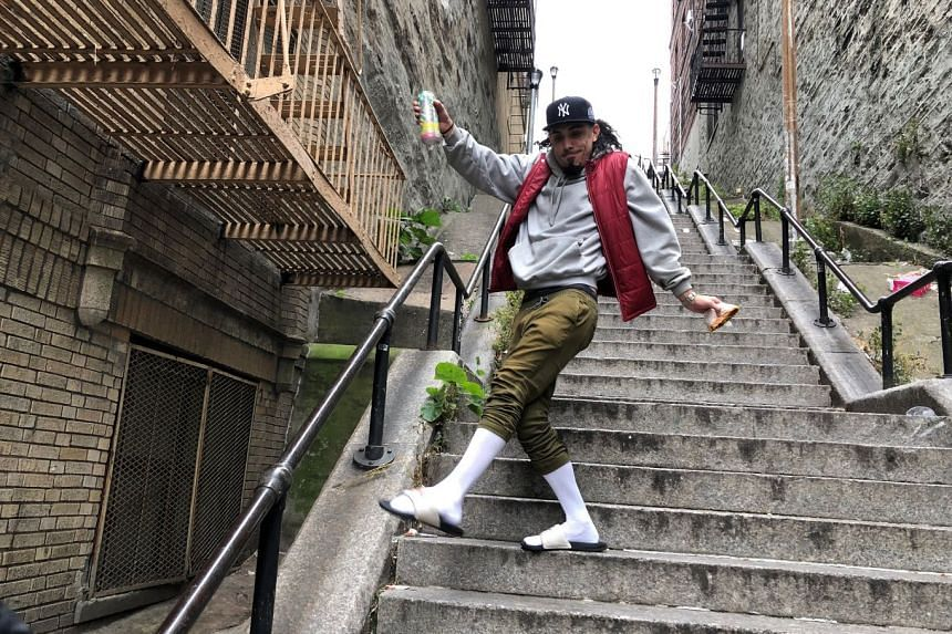 """Jay Garcia, a radio host from Queens, dances down the """"Joker Steps"""" in the Bronx borough of New York."""