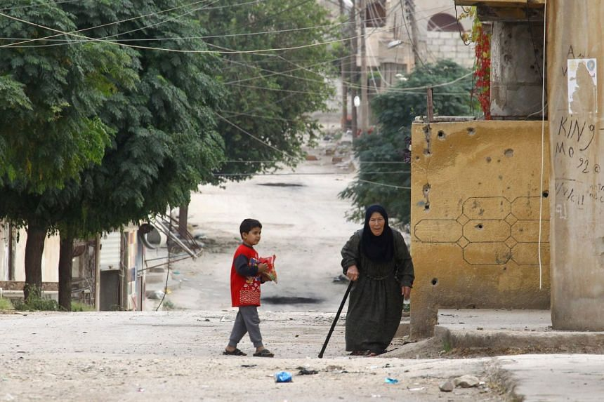 An elderly woman and a child are seen on a deserted street in the town of Ras al-Ain, Syria, Oct 24, 2019.