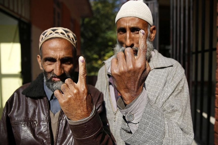 Village heads showing the indelible ink on their fingers after casting their votes in the first-ever Block Development Council polls in Chek Dara on the outskirts of Srinagar yesterday.