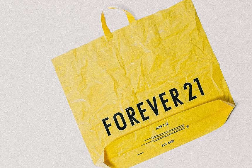 "A shopping bag (below) stamped with ""John 3:16"", a reference to a Bible verse, an example of how the family's Christian faith played a role in their running of the company. Forever 21 founder Chang Do Won with his daughters Linda (far left) and Esthe"