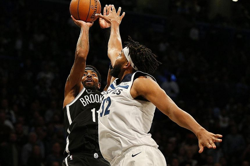 Minnesota Timberwolves centre Karl-Anthony Towns attempting to block a shot by Brooklyn Nets guard Kyrie Irving during their NBA game at the Barclays Centre on Wednesday. Despite Irving's 50 points, Minnesota won the contest 127-126 in overtime. PHOT