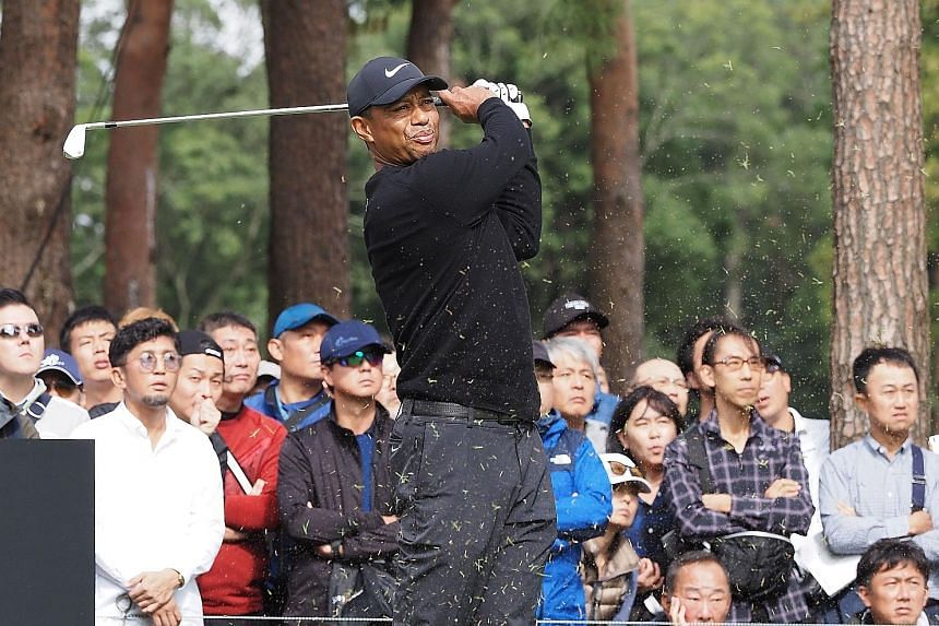 Tiger Woods teeing off at the second hole in the first round of the Zozo Championship yesterday, with huge crowds trailing after him at the Narashino Country Club course. PHOTO: AGENCE FRANCE-PRESSE