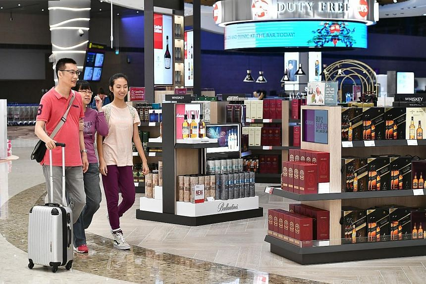 Customers (above) carrying Lotte Duty Free shopping bags in Seoul. The South Korean operator will take over the 18 liquor and tobacco concession stores managed by DFS (left) at Changi Airport next year.