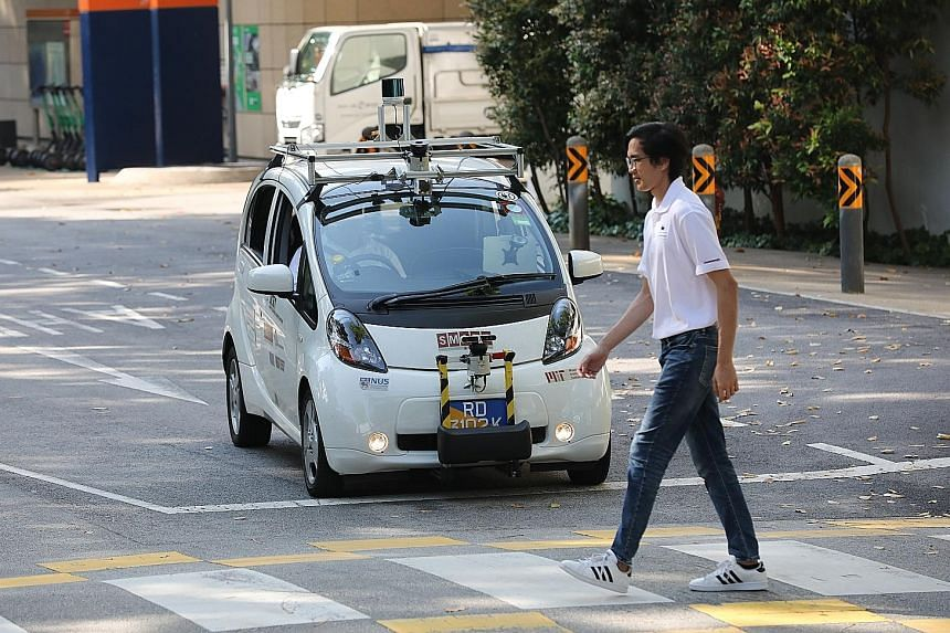 A self-driving electric vehicle being tested on the road in University Town at the National University of Singapore. All autonomous vehicles will have to display prominent decals and have markings to ensure easy identification by other road users. ST
