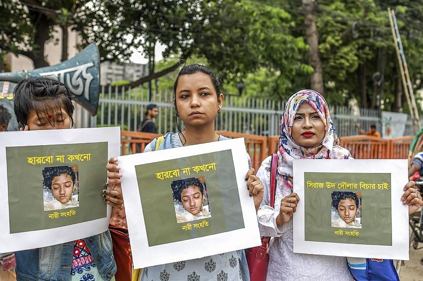 Women at a protest in Dhaka in April, holding placards that show a photograph of Ms Rafi, who died in hospital five days after being set on fire by her attackers. PHOTO: AGENCE FRANCE-PRESSE Siraj Ud Doula, the headmaster of the school where Ms Rafi