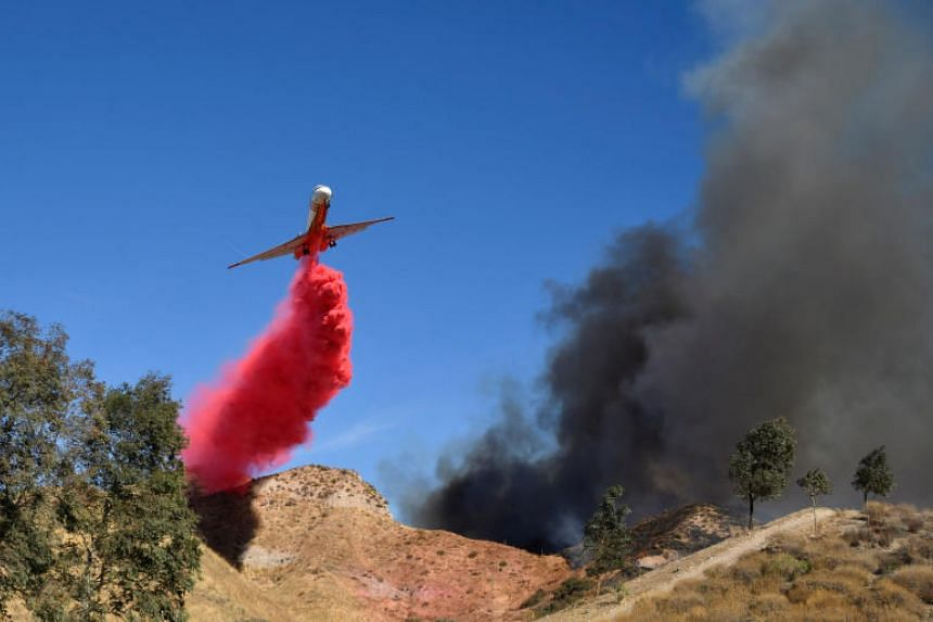 Air tankers make drops to help firefighters battle a wind driven wildfire in the hills of Canyon Country north of California, on Oct 24, 2019.