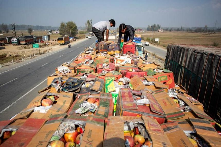 Men loads pack of apples on a truck on a national highway in the south of Kashmir on Oct 25, 2019.