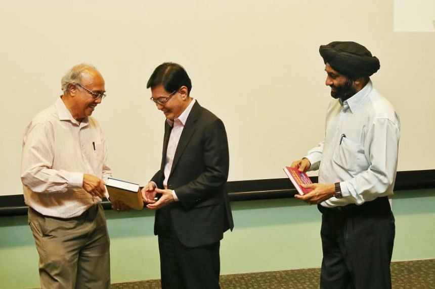 Associate Professor S. Vasoo (left) and Associate Professor Bilveer Singh (right), presenting Deputy Prime Minister Heng Swee Keat with a copy each of the two newly launched books.