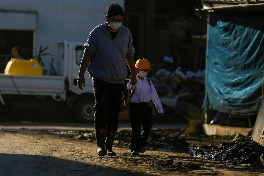 A man walks with his son near flooded houses in the aftermath of Typhoon Hagibis, in Yanagawamachi district, Date City, Fukushima prefecture, on Oct 16, 2019. At least 82 people were killed when Hagibis lashed central and eastern Japan.
