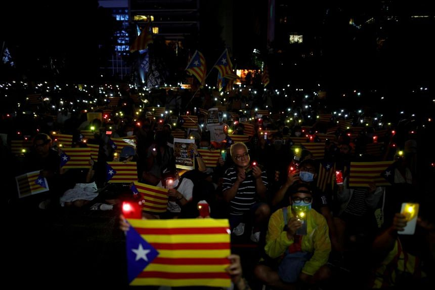 """Hundreds of Hong Kong protesters, some waving Catalan flags and banners urging """"a fight for freedom together"""", rallied in support of a separate Catalonia."""