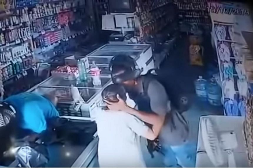 In security footage, one of the robbers can be seen tapping the elderly woman's shoulder as if he is trying to calm her down, before kissing her on the forehead.