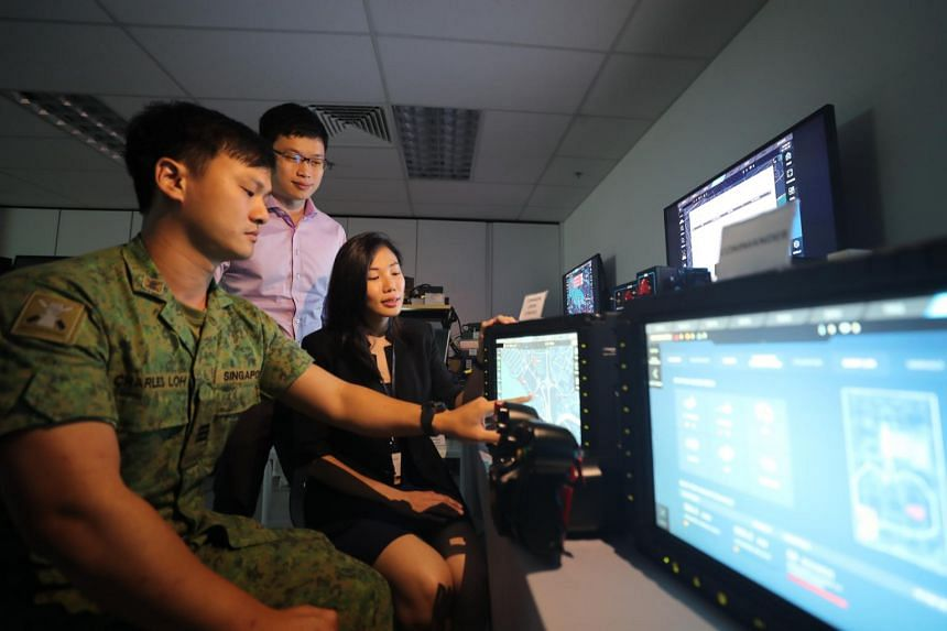(From left) HQ Armour Systems Staff Officer, Captain Charles Loh, DSTA Land Systems Programme Centre Programme Manager Bryan Ng, and ST Engineering System Consultant Zhang Guirong using the technology in the Hunter Vehicle.