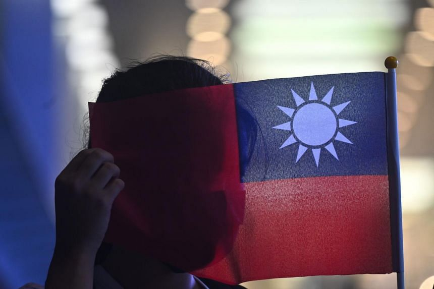 In a photo taken on Oct 10, 2019, a woman holds a Taiwanese flag to cover her face as as she joins others at a rally to mark Taiwan's National Day, in Hong Kong.