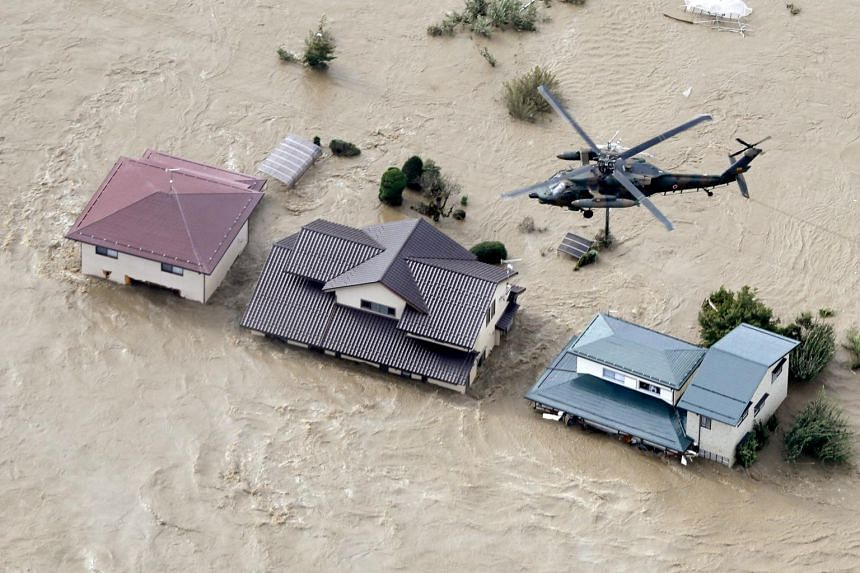 An aerial view of a Japan Self-Defence Force helicopter flying over residential areas flooded by the Chikuma river following Typhoon Hagibis in Nagano, Japan, on Oct 13, 2019.