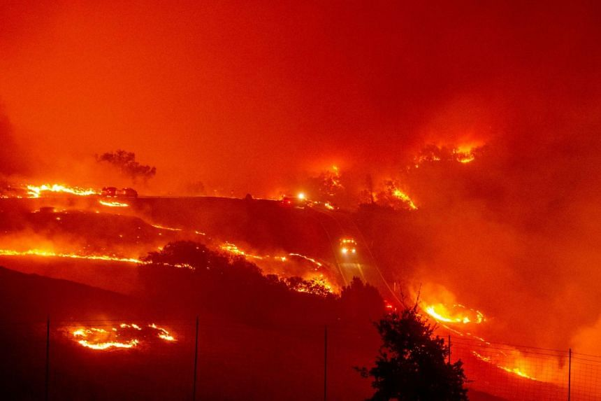 Fire trucks navigate roads surrounded with fire, as wind and embers rip through the area during the Kincade fire near Geyserville, California.