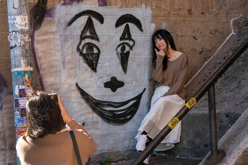 A woman poses next to a Joker face painted on the staircase in the Bronx, made famous by the movie Joker.