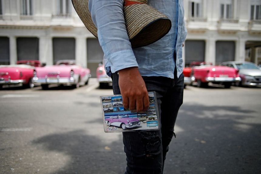 A taxi driver waits for tourists at a park in Havana, Cuba.