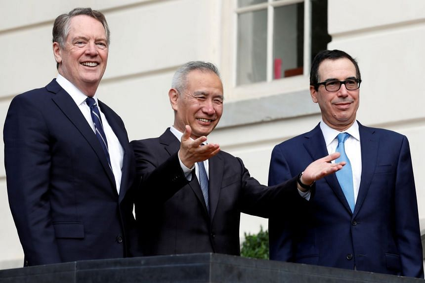 China's Vice-Premier Liu He gestures to the media between US Trade Representative Robert Lighthizer (left) and Treasury Secretary Steve Mnuchin before the two countries' trade negotiations in Washington, Oct 10, 2019.