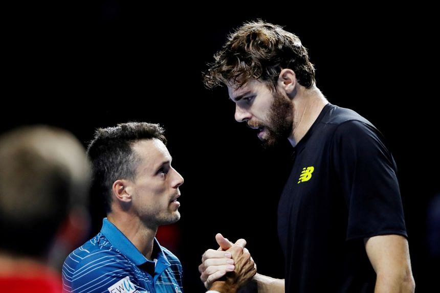 Opelka shakes hands with Spain's Roberto Bautista Agut after winning their quarter-final match.