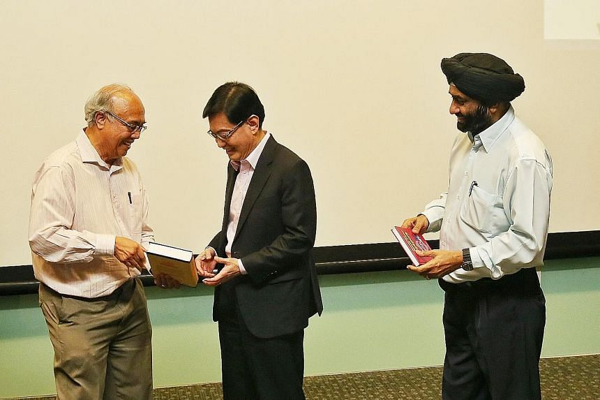 National University of Singapore associate professors S. Vasoo (left) of the social work department and Bilveer Singh of the political science department presenting Deputy Prime Minister Heng Swee Keat with the books at the launch at the Ngee Ann Kon