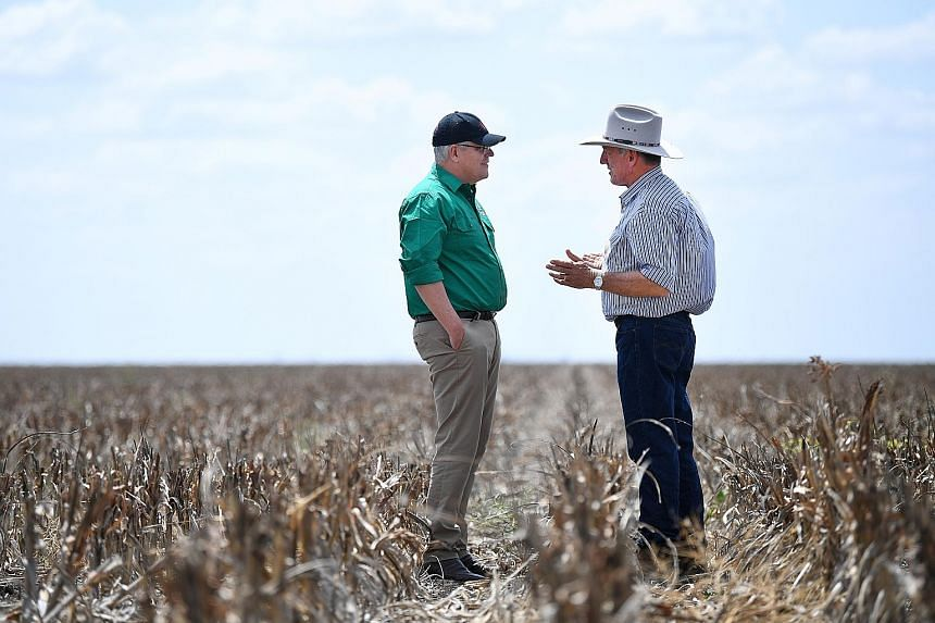 Australian Prime Minister Scott Morrison (left) speaking to a farmer on his drought-affected property near Dalby, Queensland, last month. Mr Morrison's willingness to pray and discuss his faith publicly has helped him to present himself as a straight
