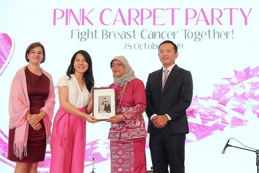 President Halimah Yacob presenting a Portrait of Hope to breast cancer survivor Cindy Neo, seen here with National Cancer Centre Singapore (NCCS) medical director William Hwang and BMW Group Asia director of sales Veronika Hammond, at the NCCS Pink Carpet
