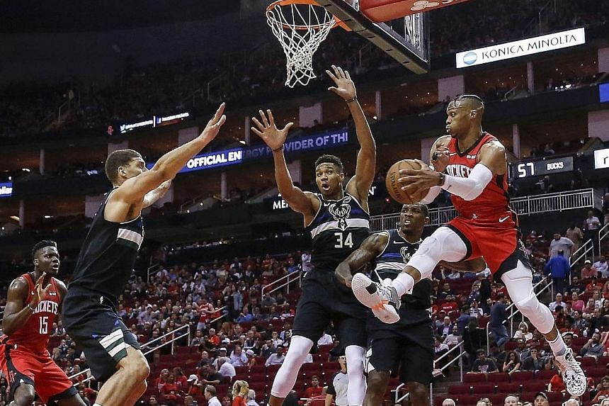 Russell Westbrook looking to pass under a basket guarded by the Milwaukee Bucks' Giannis Antetokounmpo (No. 34). He could not drag the Houston Rockets to a win in his first game since his summer move from the Oklahoma City Thunder.