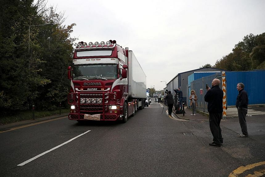 """Police moving the truck container where the bodies were discovered in Grays, Britain, on Wednesday. Beijing urged the British authorities to """"severely punish the criminals involved in the case"""". PHOTO: REUTERS"""