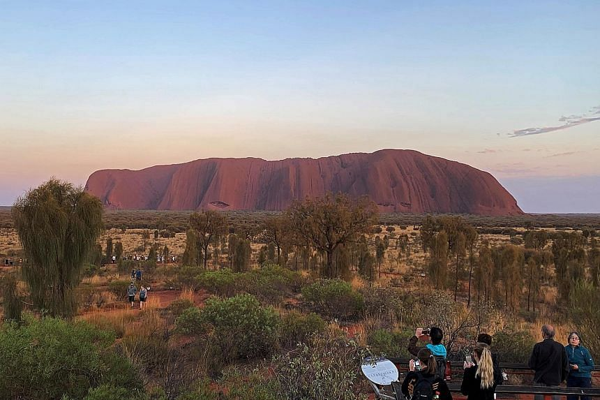 (Above) Visitors viewing Uluru, also known as Ayers Rock, yesterday, a day before a permanent ban on climbing the sacred monolith took effect following a decades-long fight by indigenous people to close the trek. (Right) Hundreds of tourists scaling