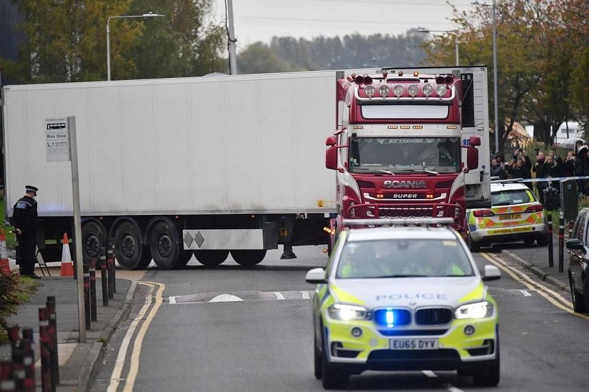 Police officers drive away a lorry (centre) in which 39 dead bodies were discovered.