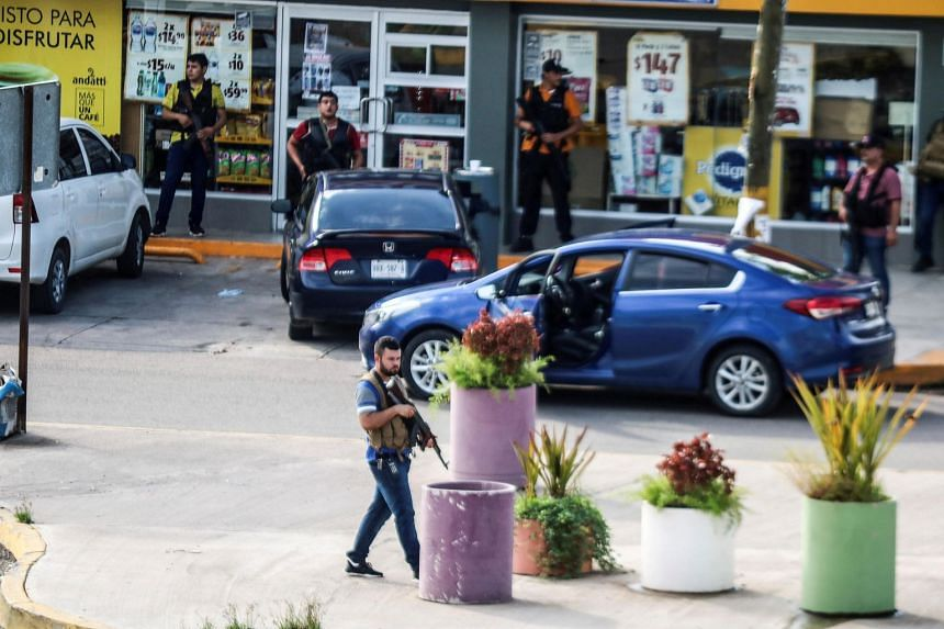 """In a photo from Oct 17, 2019, cartel gunmen are seen outside during clashes with federal forces following the detention of Ovidio Guzman, son of drug kingpin Joaquin """"El Chapo"""" Guzman in Culiacan, Mexico."""