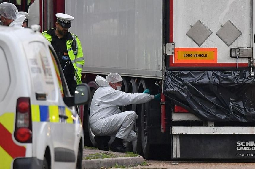 British Police forensics officers work on a lorry, found to be containing 39 dead bodies, at Waterglade Industrial Park in London, on Oct 23, 2019.