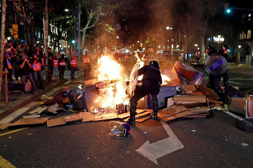Catalan regional riot police try to put out a barricade blaze during a protest in Barcelona.