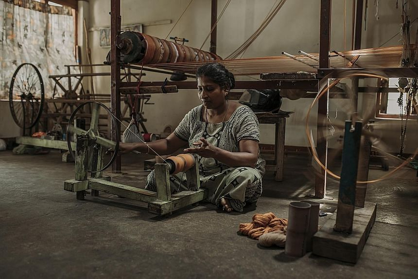 A woman turns the spinning wheel in her home. The craft of weaving is a kindred affair with whole communities involved in all parts of the process.