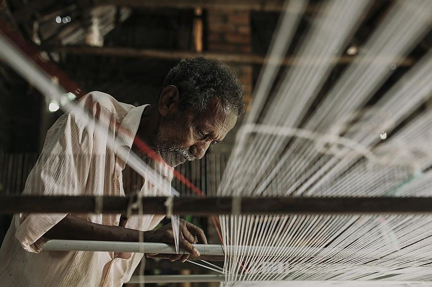 Line by line, a weaver lays the thread down in preparation for the loom.