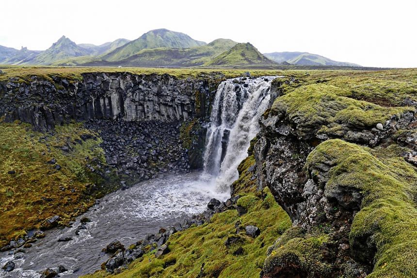 A majestic waterfall along the Laugavegur trail in the Southern Highlands of Iceland.