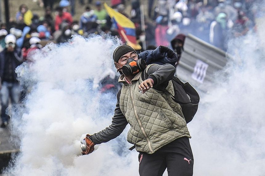 Clashes in Barcelona on Oct 18. Protesters converged for a mass show of dissent over the jailing of nine Catalan separatist leaders. PHOTO: AGENCE FRANCE-PRESSE A demonstrator throwing a tear gas canister at the riot police in Ecuador during a protes