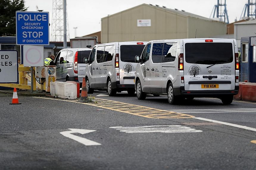 Vehicles from a funeral home arriving at the Port of Tilbury where the bodies of those found in the truck container are being held by the authorities. How the victims came to be in the truck is not yet known.