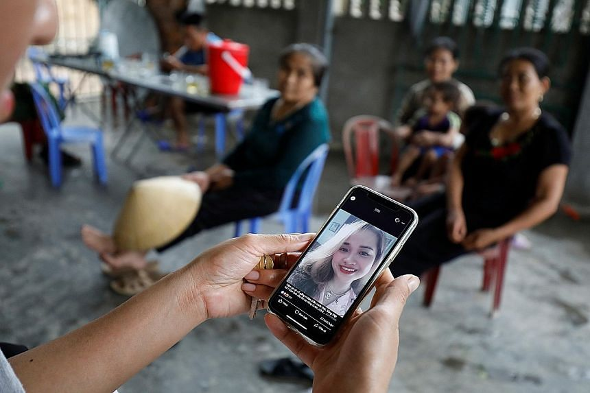 A relative in Vietnam looking at an image of Ms Bui Thi Nhung, 19, one of those feared to be among the 39 people found dead in a truck container near London. Vietnam's Prime Minister Nguyen Xuan Phuc yesterday ordered an investigation into human traf