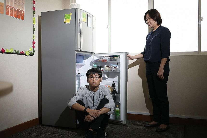 Mr Wayne Kee's (far left) OCD made him carry out repetitive tasks like opening and closing the refrigerator door for hours. When he got tired, he would ask his mother, Ms Evelyn Chng (left), to take over. OCD sufferer Vera rewrote her school notes re