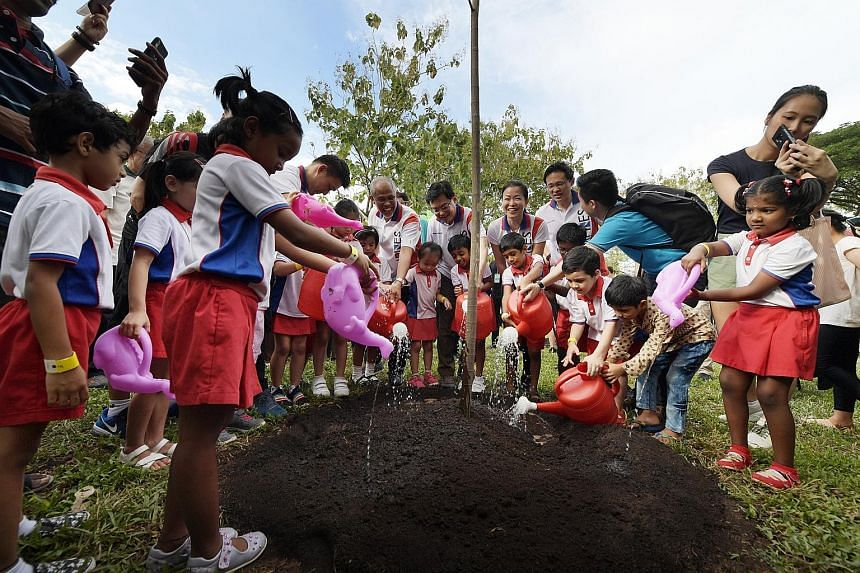 Pupils from PAP Community Foundation (PCF) Sparkletots planting a terap tree together with (centre, from left) Senior Parliamentary Secretary for Culture, Community and Youth, and Transport Baey Yam Keng; Minister for the Environment and Water Resour